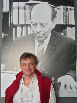 オルケーニ氏の肖像写真の前に立つ芸術監督マーチャイ氏 photo by Mana KATSURA