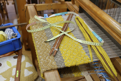 緻密な模様で織られていく織物