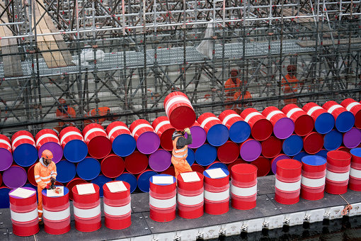 2018年5月の『The London Mastaba』建設風景。作業員がドラム缶を積み上げている。 Workers installing barrels on the vertical side of the London Mastaba, May 2018, Photo: Wolfgang Volz
