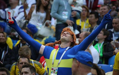 サポーターの持つカップにはバドワイザーのロゴ 作者 Кирилл Венедиктов (soccer.ru) [CC BY-SA 3.0 GFDL, CC BY-SA 3.0  (https://creativecommons.org/licenses/by-sa/3.0) または GFDL (http://www.gnu.org/copyleft/fdl.html)], via Wikimedia Commons