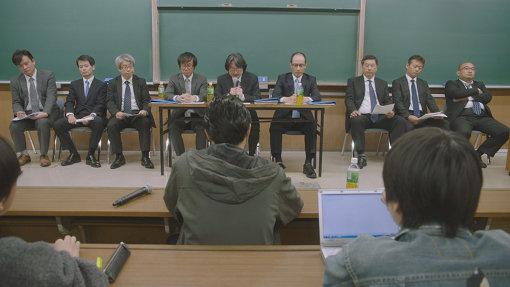 学生側と大学側の交渉のシーン