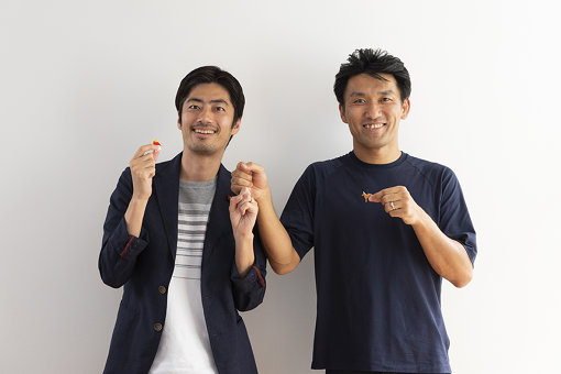 左から、「この指とまれ」ポーズの小国士朗さんと、唐川靖弘