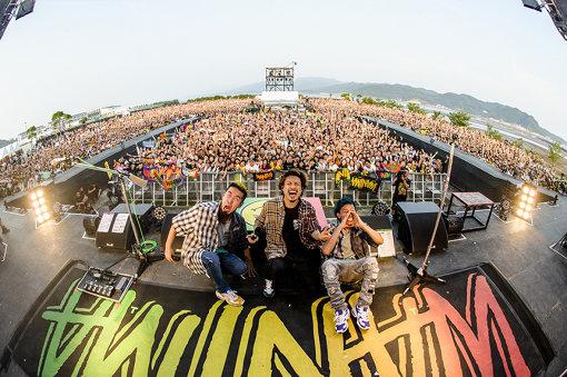 左から:FUJI、KENTA、KO-SHIN<br>プロフィール:WANIMA(わにま)<br>KENTA(Vo,Ba)、KO-SHIN(Gt,Cho)、FUJI(Dr,Cho)による、熊本県出身の3ピースロックバンド。2010年結成。2014年10月、PIZZA OF DEATH RECORDSから『Can Not Behaved!!』でデビュー。2017年5月よりunBORDEとタッグを組み、2018年1月にリリースしたメジャー1stフルアルバム『Everybody!!』は35万枚を超えるセールスを記録。同作のツアーファイナルでは、メットライフドーム2daysで7万人を動員した。2019年3月6日に4thシングル『Good Job!!』をリリース、さらに7月17日には5th『Summer Trap!!』を発表し、10月23日には2ndアルバム『COMINATCHA!!』をリリースし、アルバムとして2作連続で週間チャート1位を獲得。