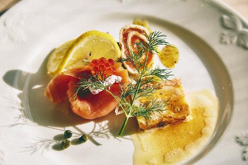 ノルウェーサーモン3種の前菜、北欧ならではの調理法=保存法で3種(スモークサーモン・サーモンマリネのクレープ包み、はち蜜マスタードソース・サーモンプディング、ローストバターソース)