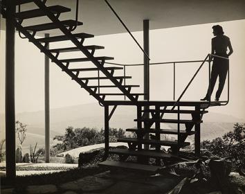 ガラスの家、ピロティから2階への階段に立つリナ。(1951年 Francisco Albuquerque撮影)