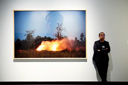 アピチャッポン・ウィーラセタクン。『ゴースト・ティーン』が『炎』にうっすら映っている。各作品が関係し合うような展示レイアウトが特徴的 /『炎』2009年 インクジェット・プリント 東京都写真美術館蔵