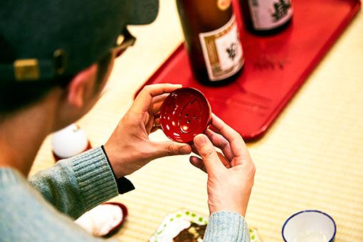 「新潟」をテーマにしたとんぼせんせいの朱器。日本酒を注ぐ酒器に原材料であるお米を描いたユニークなデザイン