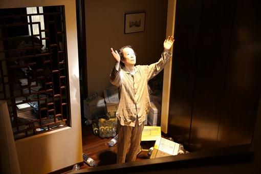 映画『美しい星』より。突然の激しい揺れの後、玄関から降り注ぐUFOと思しきものによる不思議な光のなかに進み出る大杉重一郎(リリー・フランキー) / ©2017「美しい星」製作委員会