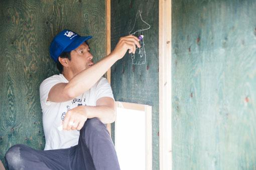 インタビューを受けながら、小屋のなかの壁や床に絵を描き始めた