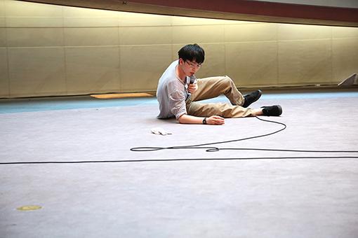 関川航平『片耳をふさぐ』(2017年)スパイラルで行われたいくつかの過去に見た風景についてと、実際にパフォーマンスをしている場所から見える風景についてをごちゃまぜにして、即興で喋りつづけるパフォーマンス作品。 撮影:市川勝弘 画像提供:スパイラル / 株式会社ワコールアートセンター