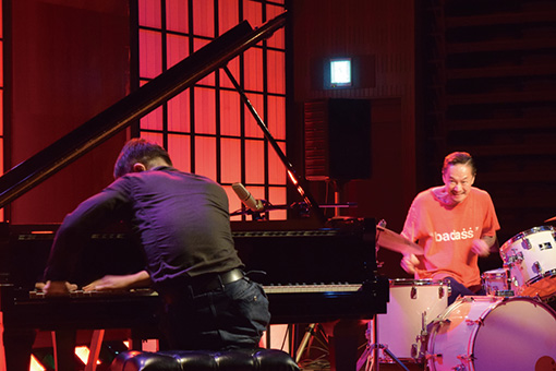 チトセピアホールで行われたドラマー・中村達也とピアニスト・スガダイローのデュオ「赤斬月」のセッション / ホールの客席部分にグランドピアノとドラムセットを置いた特設ステージでの演奏が行われた