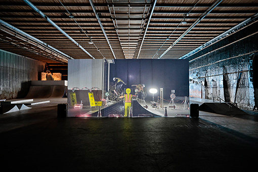 『SIDECORE - rode work』よりEVERYDAY HOLIDAY SQUAD『RODE WORK』(2017年)展示風景 ©Reborn-Art Festival 2017 / 工事現場の作業着姿でスケートボードをする映像