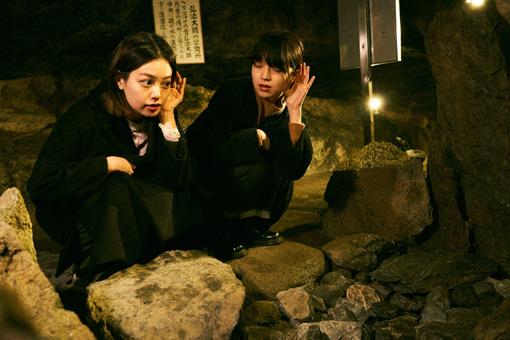 水琴窟(すいきんくつ)にて、岩の下に隠れた、水を張った龜(かめ)に落ちる雫の音に耳を傾ける二人