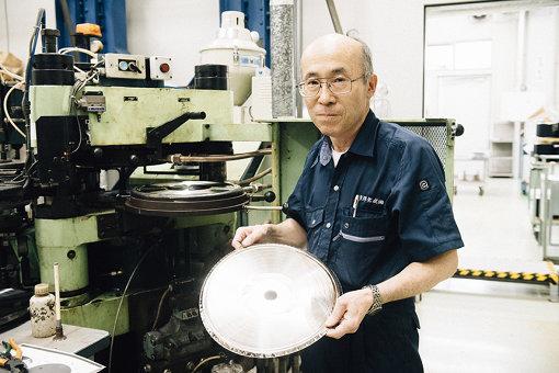 プレス作業の粟野張男(東洋化成)。手塚とほぼ同時期に東洋化成へ入社し、長きに渡りレコードをプレスし続けてきた