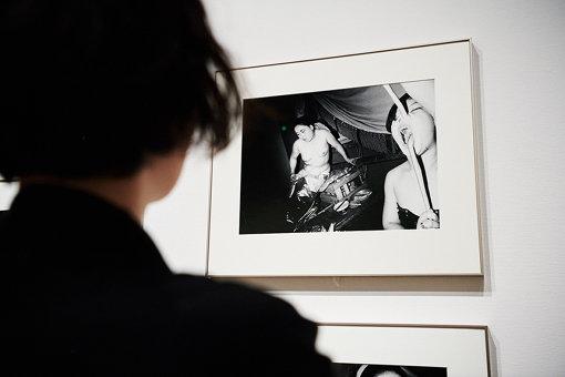 見世物小屋の光景を写した作品を観入る鳥居。