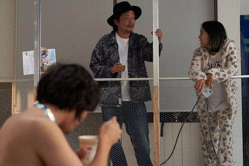 Chim↑Pom『にんげんレストラン』会場内、鎖に繋がれて物乞いする松田修のパフォーマンス『人間の証明1』前にて