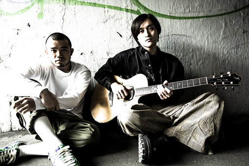 左から:アフロ(MC)、UK(Gt)<br>MOROHA(もろは)<br>2008年結成。アコースティックギターのUKと、マイクに喰らいつくMCのアフロからなる2人組。楽曲、ライブともにGt×MCという最小最強編成で臨み、「対ジャンル」ではなく「対人間」を題目に活動。2018年に『MOROHA BEST~十年再録~』でメジャー進出。ライブハウス、ホール、フェス、場所を問わず聴き手の人生へと踏み込む楽曲を生み出し続ける。