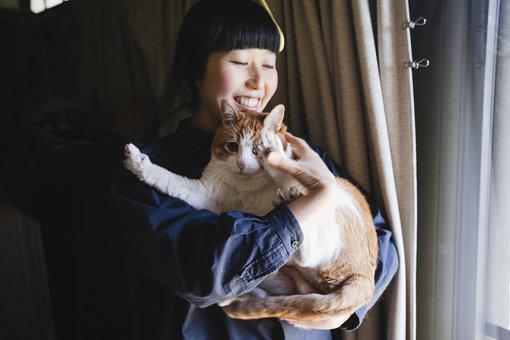 抱き上げられて暴れる猫のテリー