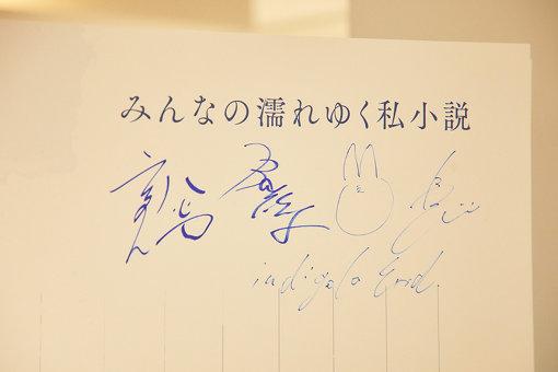 来場者が書き込めるパネルに、メンバーもサインを入れた。