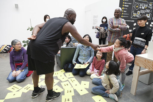 『アートセンターをひらく 第Ⅰ期』では、合計6名の作家が滞在した。参加作家のひとりハロルド・オフェイによる観客の指示によって作り上げるパフォーマンス『Choreograph Me』(振りつけて)の様子 / 撮影:松本美枝子 写真提供:水戸芸術館現代美術センター