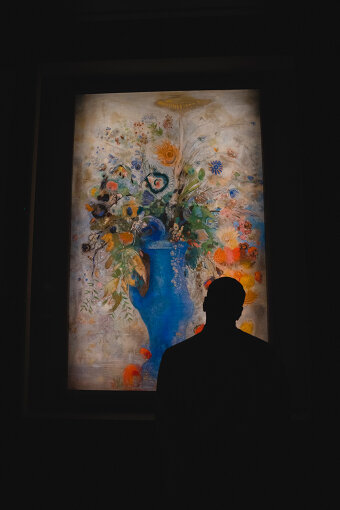オディロン・ルドン『グラン・ブーケ(大きな花束)』(1901年 / 三菱一号館美術館蔵)。ルドンは同世代の印象派が外界に意識を向けていたのに対し、内面の夢と想像の世界からインスピレーションを得ていた。木炭と石版画を使った「黒」の作品を多数発表していたが、1894年以降にはパステルや油彩画などの色彩の作品を発表する。「まるで後ろから光を当てているみたいですね」と口にするなど、長田は展示手法にも興味を示していた。