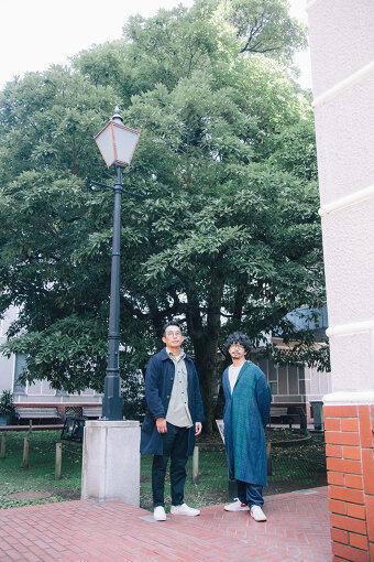 左から:釜萢直起(GREENROOM)、後藤正文(ASIAN KUNG-FU GENERATION) / この日の取材は横浜開港資料館で実施した。同館は、現在の横浜の街のあり方を決定づけた横浜開港につながる歴史的瞬間を描いた、『ペリー提督・横浜上陸の図』にも登場する「玉楠」が中庭に生い茂っている。
