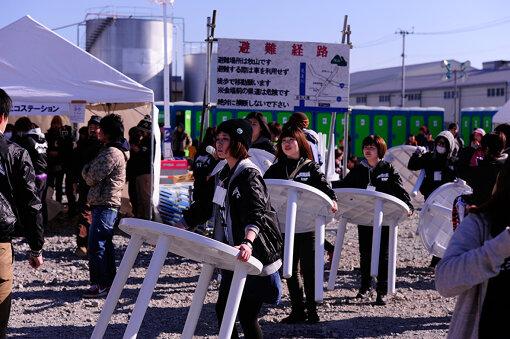 石巻で開催された『東北ジャム2013』ボランティアスタッフの活動。背後には避難経路が書かれた看板も。