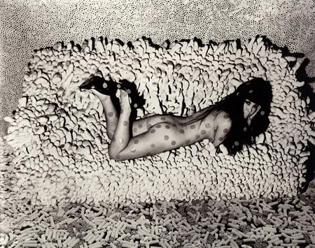 フォトコラージュ ソフトスカルプチュア「集積No2」(1962年制作)に横たわる草間。1966年 photo by Hal Reiff ©YAYOI KUSAMA
