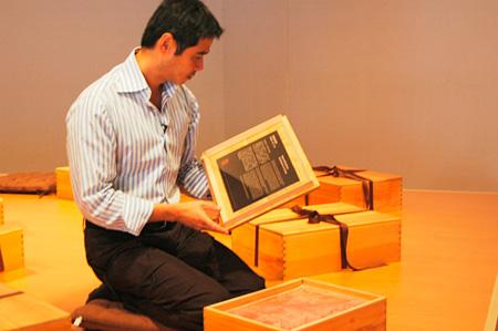 フタの内側のテキストを読むリー・ミンウェイ 台北現代美術館でのFabric of Memory 展示風景(2007年) Courtesy of MoCA Taipei