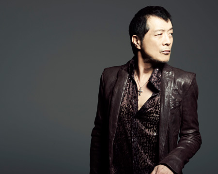 ブラウンのシャツにジャケットを着て立っている矢沢永吉の画像