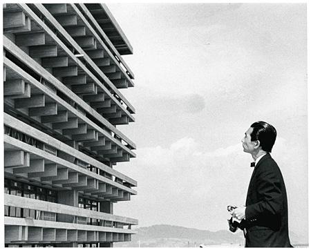 香川県庁舎カメラを手に竣工当時の香川県庁舎と対峙する丹下 1958年頃撮影 撮影者不明