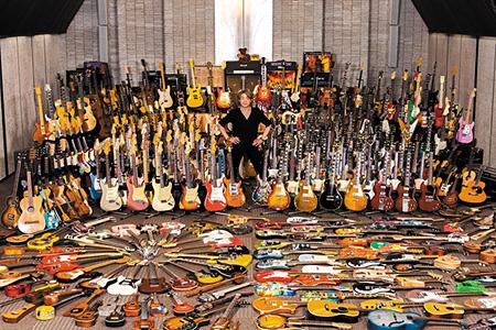 ギターコレクションの前に立つヨッちゃんこと野村義男