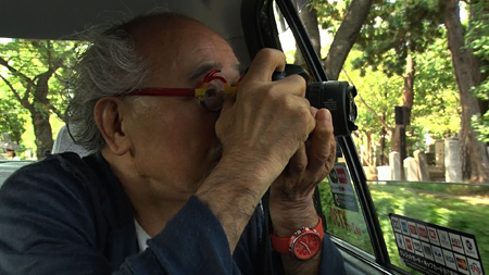 打ち砕いたレンズで撮影する荒木経惟 『日曜美術館 写狂老人'時'記 ~写真家 荒木経惟75歳の日々~』より