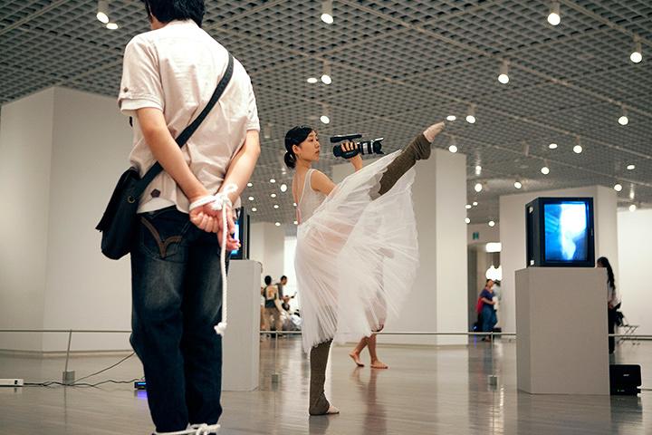 橋本聡『ビデオ撮影:バレリーナ』2012年 パフォーマンス(バレリーナが会場の様子をビデオで撮影する)(参考図版)