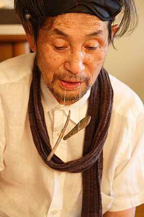 サヌカイトを口にくわえる吉増剛造 2015年 Photo: Kioku Keizo