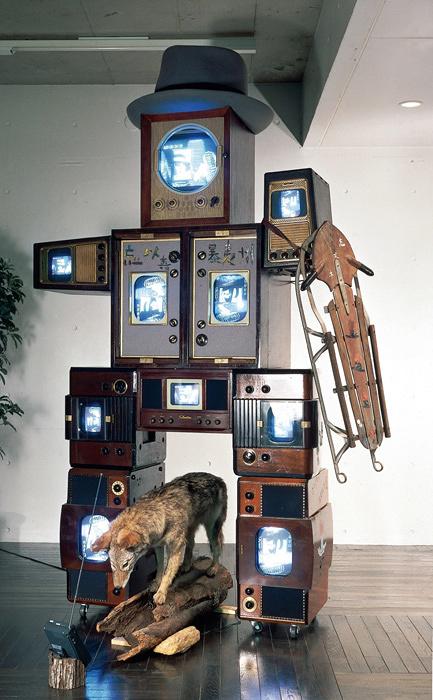 ナムジュン・パイク『ボイス』1988年 コヨーテの剝製、帽子、そり、木片、モニター11台、TVキャビネッ 10台、映像1チャンネル、再生機1台 150×270×70㎝(コヨーテ除く)