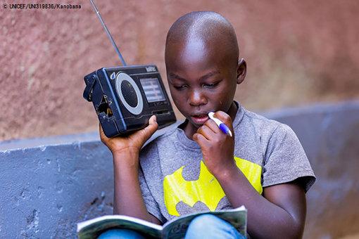 小学校が休校になり、ラジオ番組を通じて自宅で勉強する11歳の男の子。(ルワンダ、2020年4月9日撮影) © UNICEF_UNI319836_Kanobana