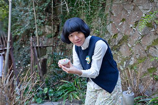 尾道市のアーティスト、園山春二が丸い石に描く「福石猫」
