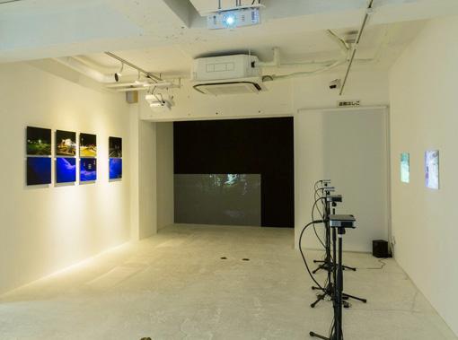 『永い風景』の展示風景。画面右側が『ヒノサト』のために撮影された映像、左側が今回の展示のために「日の里」で撮影された写真。奥に夜の東京で撮影された映像が展示されている。
