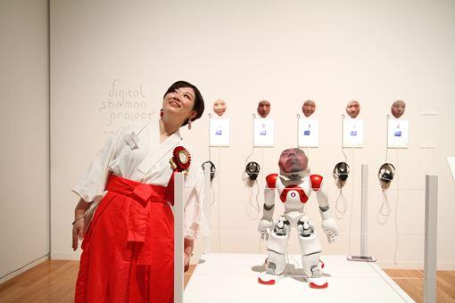 『デジタルシャーマン・プロジェクト』のロボットと同じポーズをとる市原えつこ