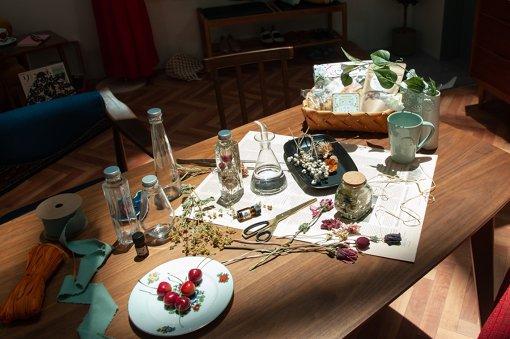 テーブルには作りかけのハーバリウムが置かれ、その傍らにはさくらんぼやおせんべいも見える