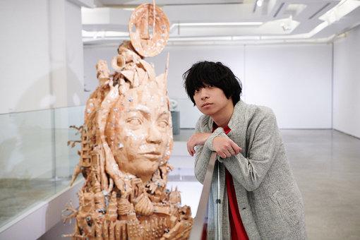 尾崎世界観。後ろの作品は、前橋出身作家の関口光太郎が本展のために制作した『SUN TOWER 2020/MAKET』
