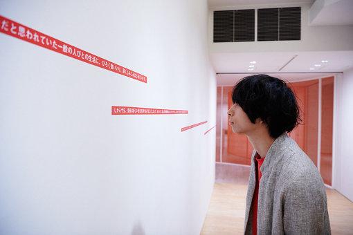 壁に貼られた岡本太郎の言葉を眺めている様子