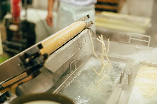 製麺され、茹でられるうどん