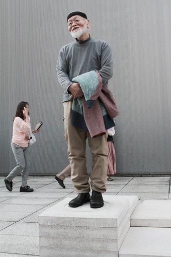 自身の作品の上に立つアーティストの鈴木昭男