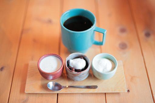 すっきり目に抽出されたコーヒーと、お猪口に入ったミルク、お豆、ホイップ