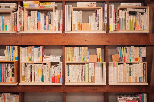 倉庫の面影を残す格子状に組まれた壁面の木材を本棚として利用している