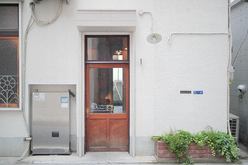 白壁と木製の扉が印象的な「東京ひかりゲストハウス」