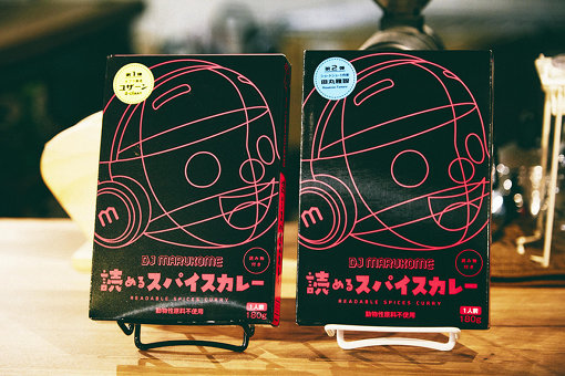 「DJ MARUKOME 読めるスパイスカレー」。左が第1弾、右が第2弾。それぞれU-zhaan(タブラ奏者)と田丸雅智による読めるコンテンツが同梱されている