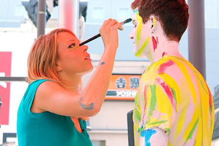 モデルの男性の全身に青や黄色の絵の具を塗るアレクサ・ミード
